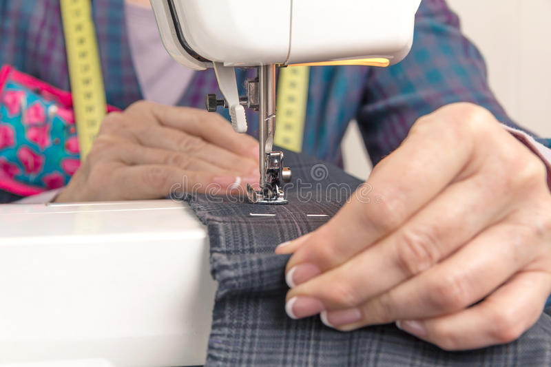 Seamstress hands working on a sewing machine. Closeup of seamstress hands working with clothing item on a sewing machine. Focus in the needle royalty free stock images