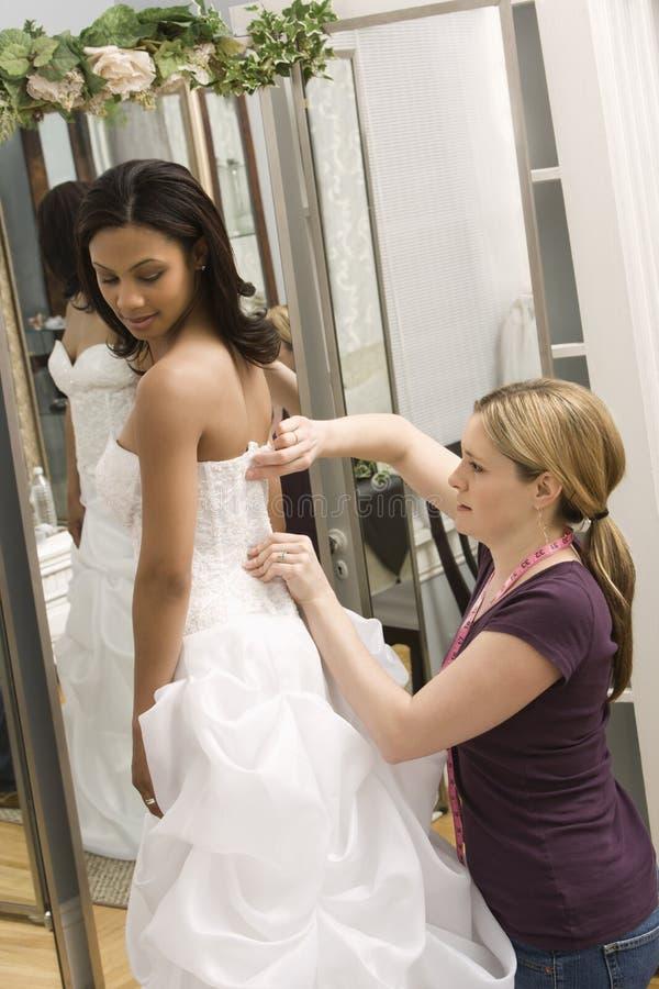 Seamstress helping bride. Caucasian seamstress helping African-American bride in bridal shop royalty free stock images