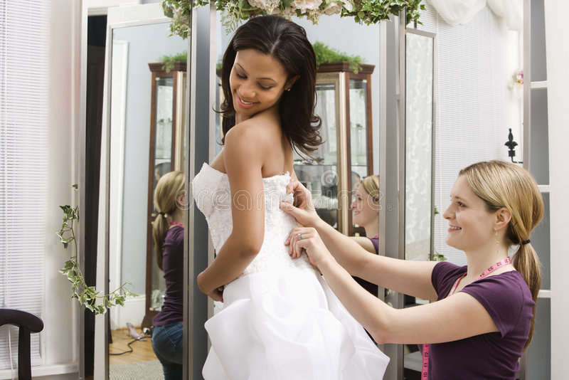 Seamstress helping bride. stock image