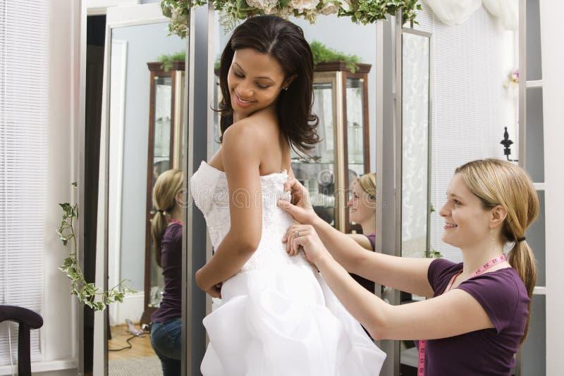 Seamstress helping bride. Caucasian seamstress helping African-American bride in bridal shop stock image