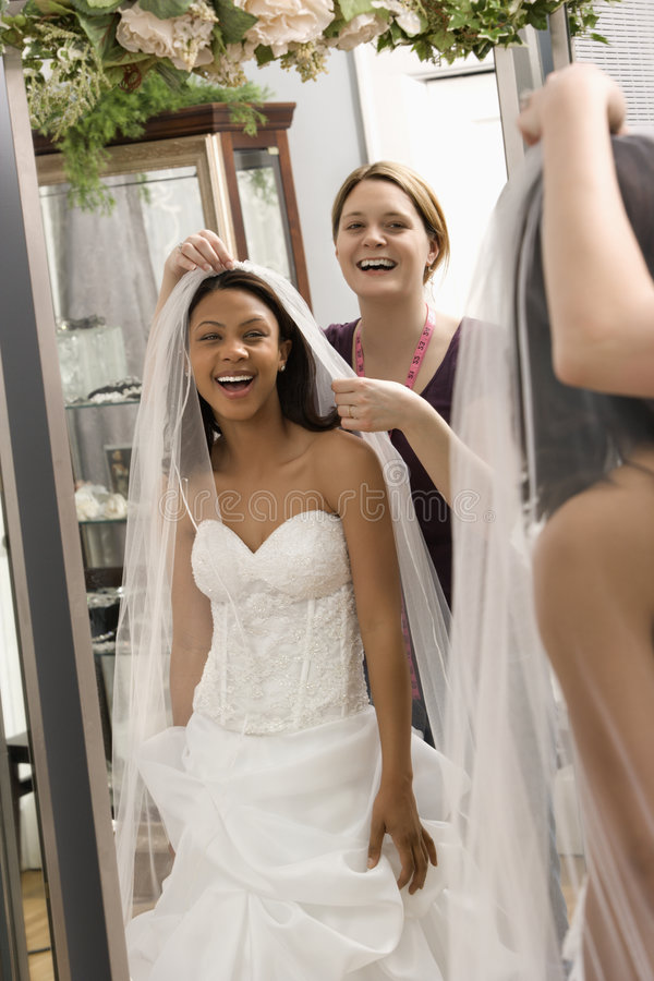 Seamstress helping bride. Caucasian seamstress helping African-American bride with veil in bridal shop stock images