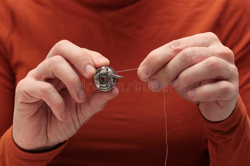 The seamstress holds the bobbin`s shuttle with his hands and pulls the thread. sewing process royalty free stock photo