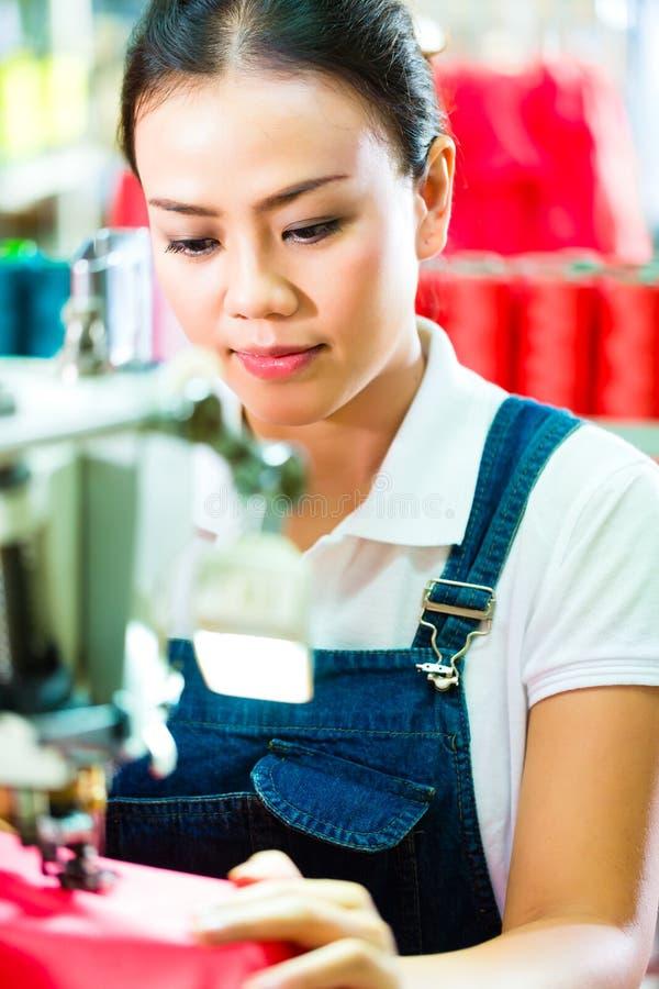 Seamstress i en kinesisk textilfabrik royaltyfri fotografi