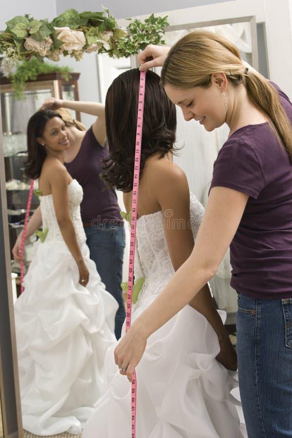 Seamstress measuring bride. Caucasian seamstress measuring African-American bride in bridal shop royalty free stock photo