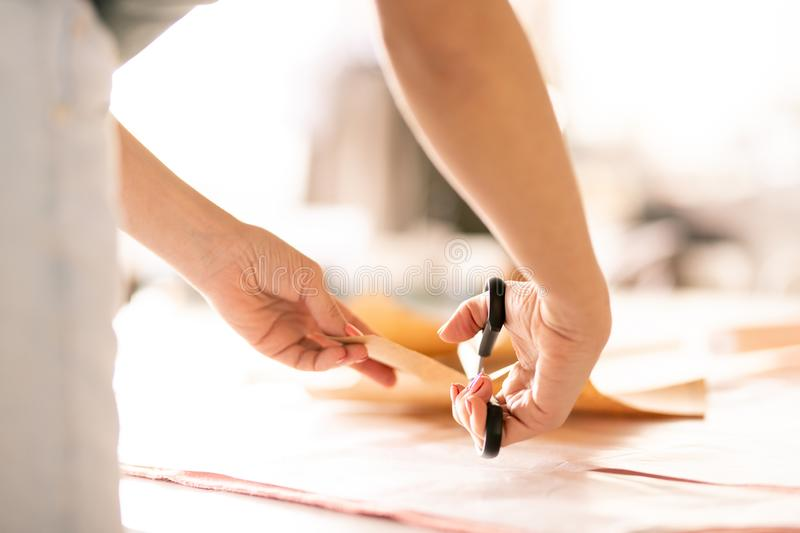 Hands of seamstress. Seamstress with scissors bending over table and cutting paper pattern while working in tailoring shop royalty free stock photos
