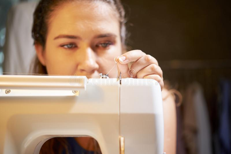 Seamstress sewing on sewing machine stock images