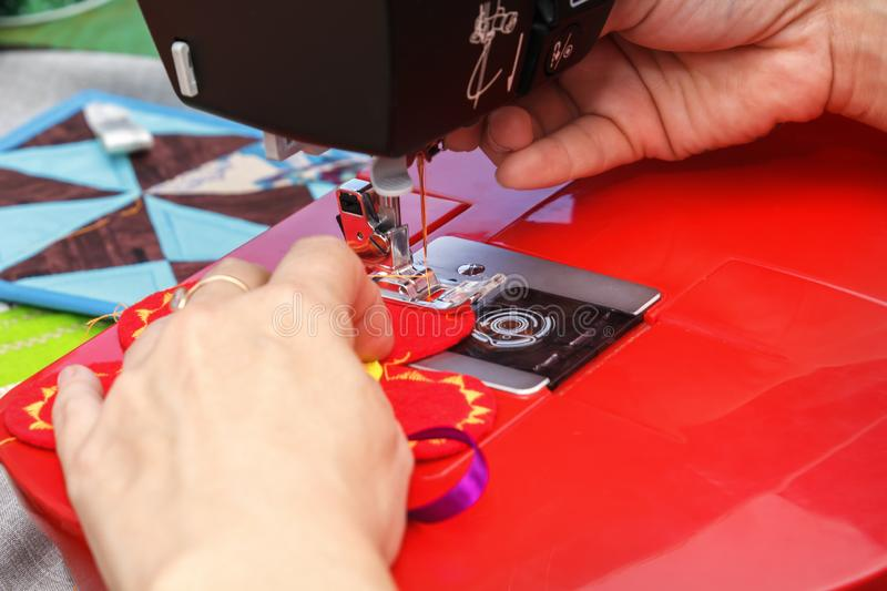 Seamstress sews material on a sewing machine. Close-up stock photo