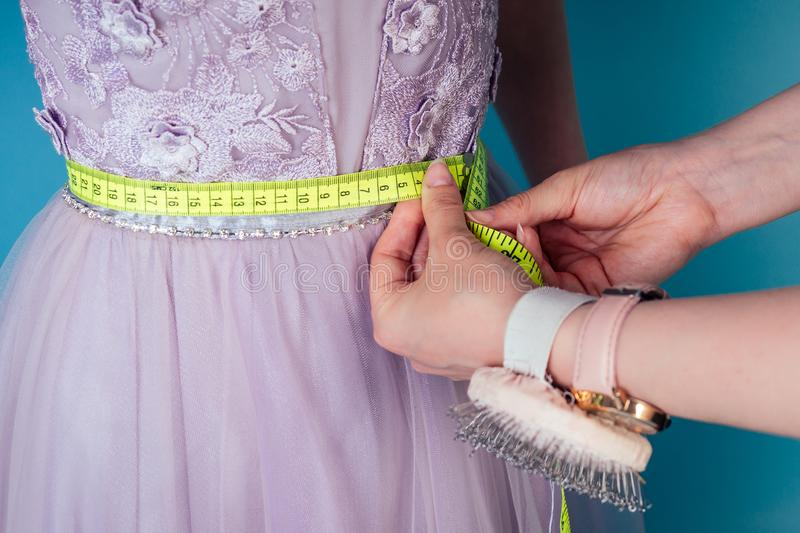 Seamstress tailor dressmaker designer wedding dress measures the volume of the client`s body measuring tape on a blue royalty free stock photos