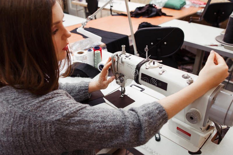 Seamstress tuning sewing machine for work stock photos