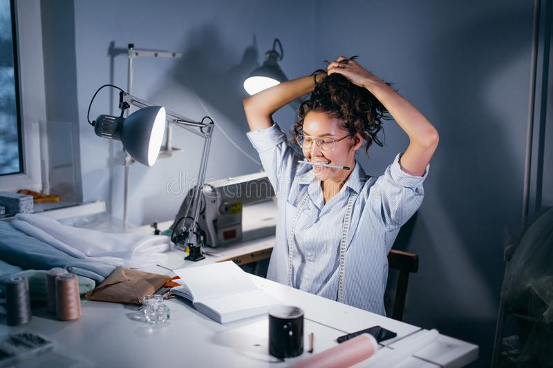 Seamstress wearing glasses with pencil on arms collecting hair at light table stock image