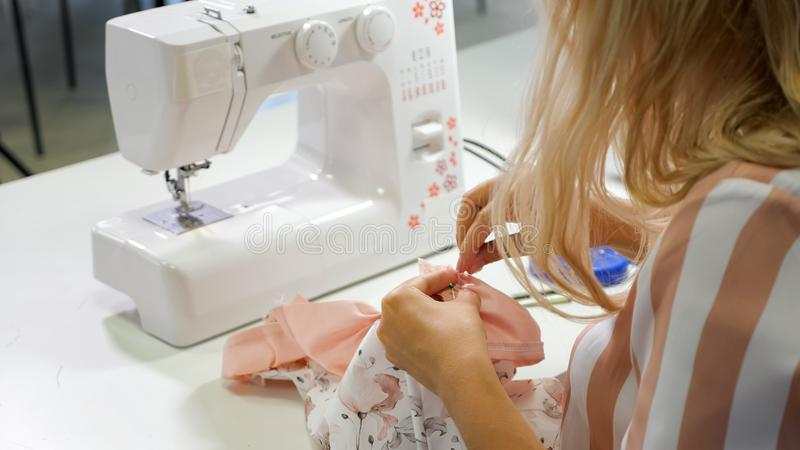 Seamstress at work in workshop sewing clothes on sewing machine stock image