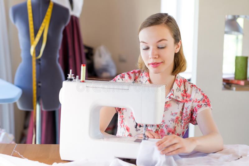 Seamstress at work. Young attractive needlewoman at studio working with sewing machine royalty free stock images