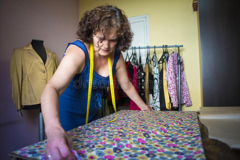 Seamstress working for the tailoring. While taking measures in a dress royalty free stock photos