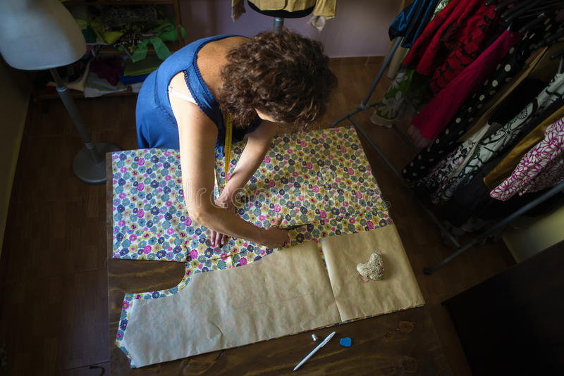Seamstress working for the tailoring. While taking measures in a pattern royalty free stock photography