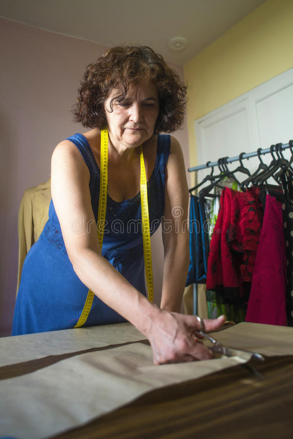 Seamstress working for the tailoring. While taking measures in a pattern royalty free stock photos