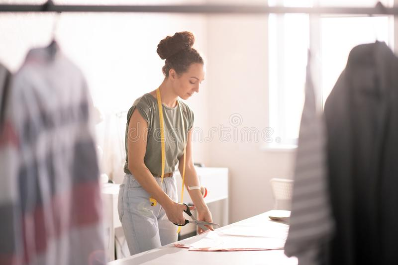 Seamstress in workshop. Pretty young seamstress standing by workplace and cutting textile close to paper pattern during work in fashion studio stock image