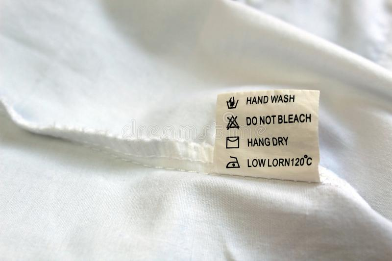 On the seamy side of the clothes there is a tag with instructions for use. Label, clothing, tag, washing, cloth, clothes, white, instructions, care, laundry royalty free stock image