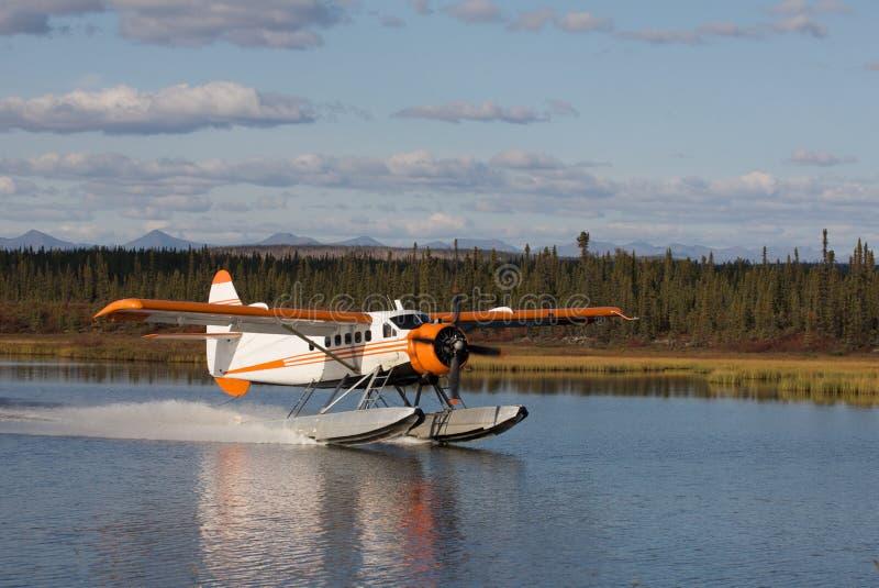 Seaplane Landing on an Alaskan Lake. Seaplane makes a landing on a calm Alaskan lake stock image