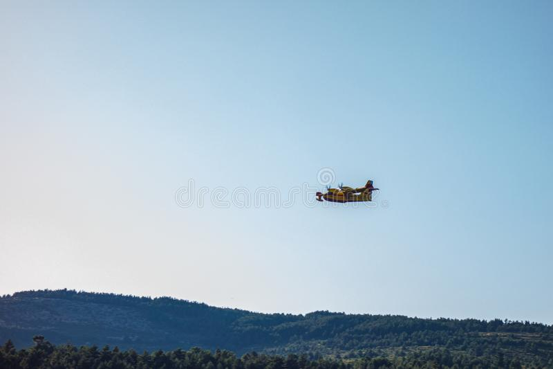 Seaplane launching water during a forest fire stock photography