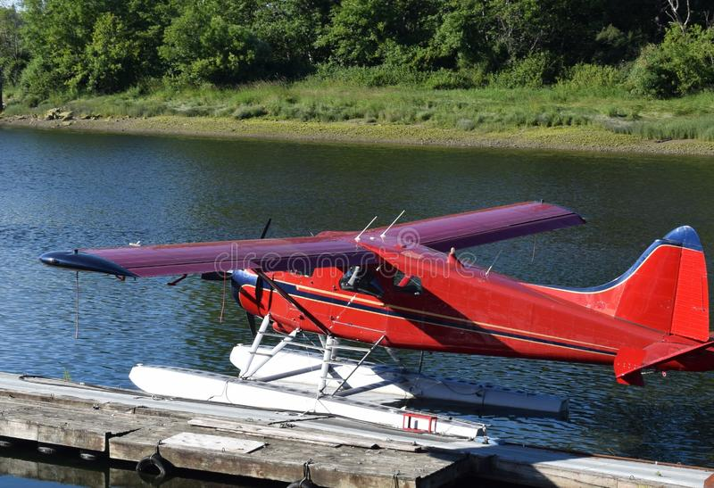 Seaplane plane moored on a jetty. Red single engine seaplane plane moored on a jetty on a river, green forest landscape in the background royalty free stock photography