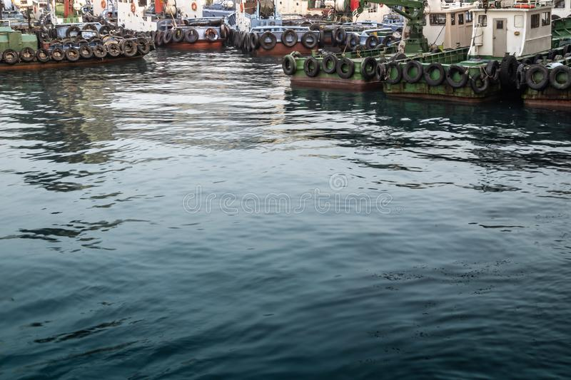 Seaport full of docking rusty fishing boats with dark water. royalty free stock images