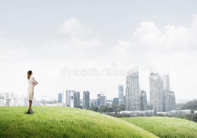 In search of development perspectives. Businesswoman standing with back on top of hill and viewing modern city royalty free stock photo