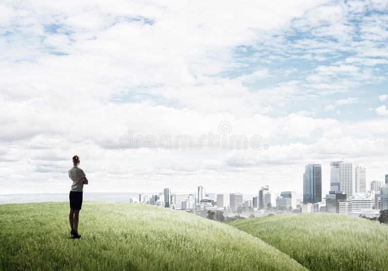 In search of development perspectives. Businesswoman standing with back on top of hill and viewing modern city stock photos
