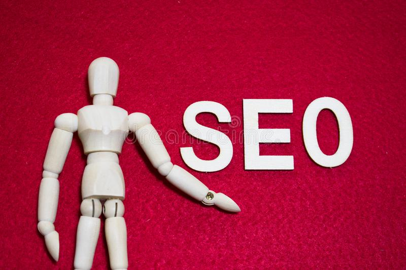 Search Engine Optimization concept SEO, Wooden puppet on red color acrylic felt fabric stock images