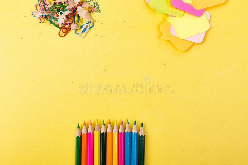 Search idea concept. Colorful pencils, stickers, clips and on yellow background. Copy space. School supplies royalty free stock photography