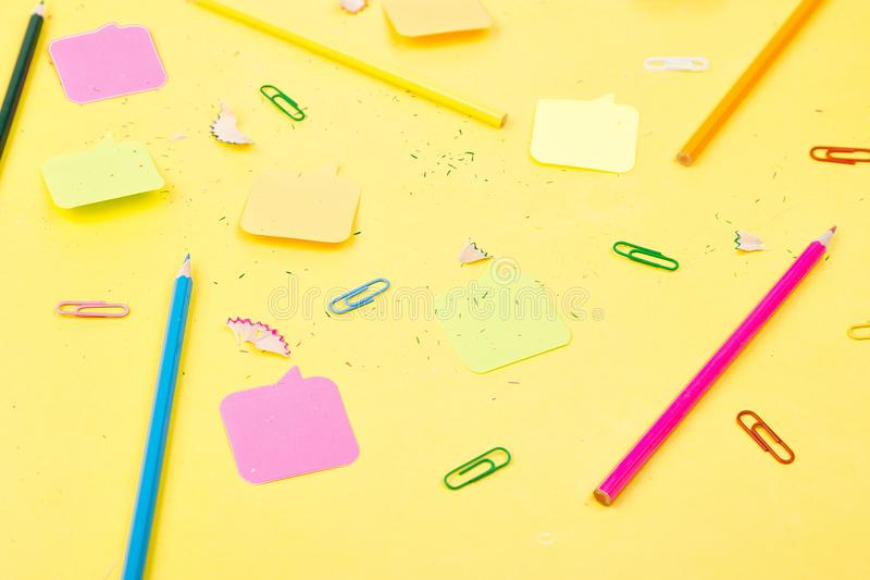 Search idea concept. Colorful pencils, stickers, clips on yellow background. School supplies. Exam, school student stock images