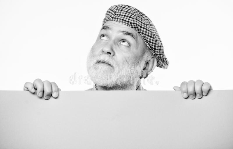 Search for inspiration. dreaming mature man in retro hat. Senior bearded man place announcement on banner. Advertisement stock images