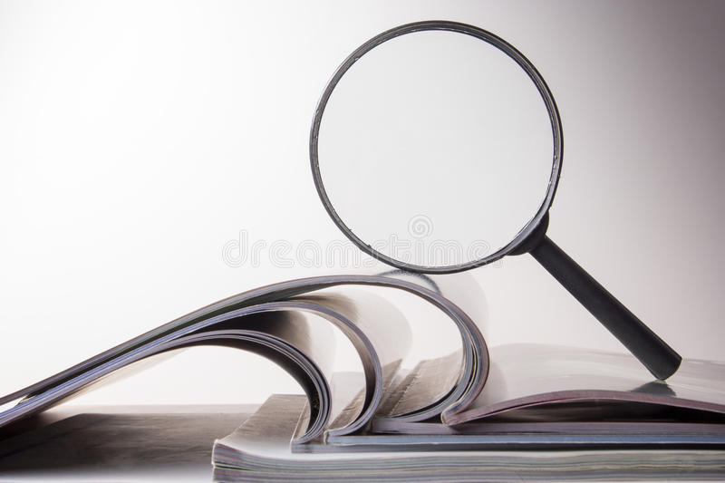 Search with magnifying glass, looking for information in books, blueprints, magazines. Audit inspection. Copy space text. Search with magnifying glass in books royalty free stock photo