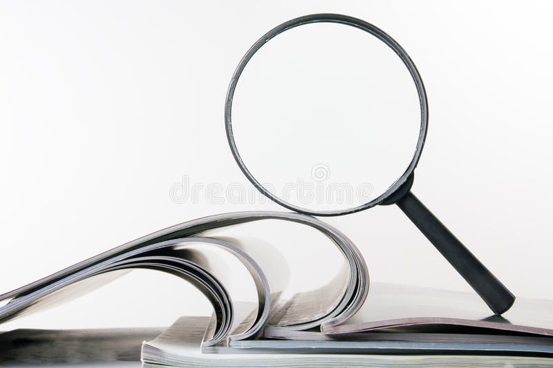 Search with magnifying glass, looking for information in books, blueprints, magazines. Audit inspection. Copy space text. Search with magnifying glass in books royalty free stock images