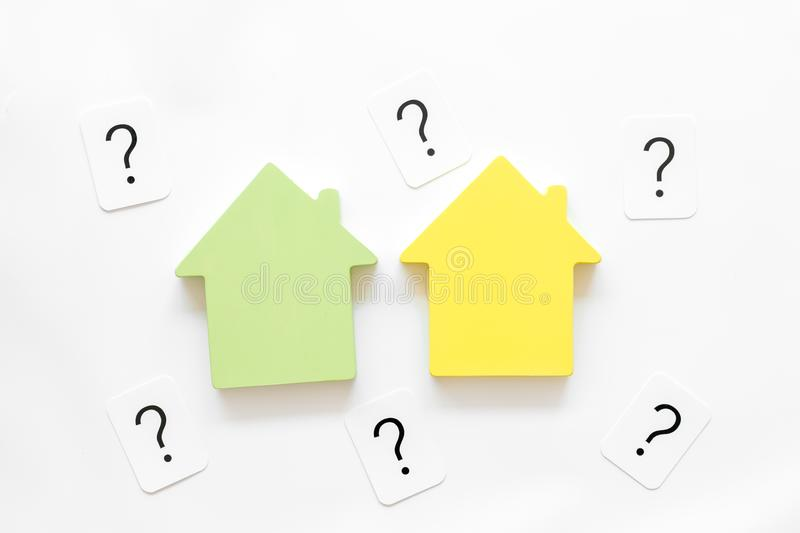 Search for a new house concept with house figure and question mark on white office desk background top view.  royalty free stock image