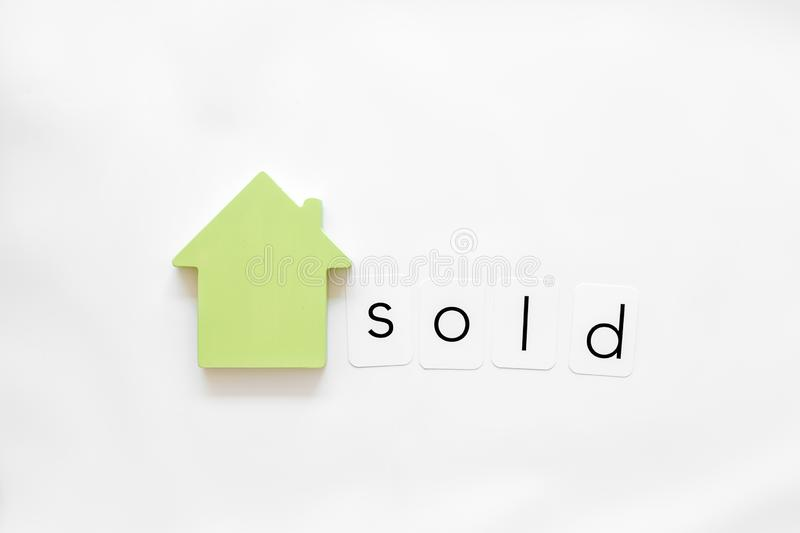 Search for a new house concept with house figure and sold copy on white office desk background top view.  royalty free stock photography