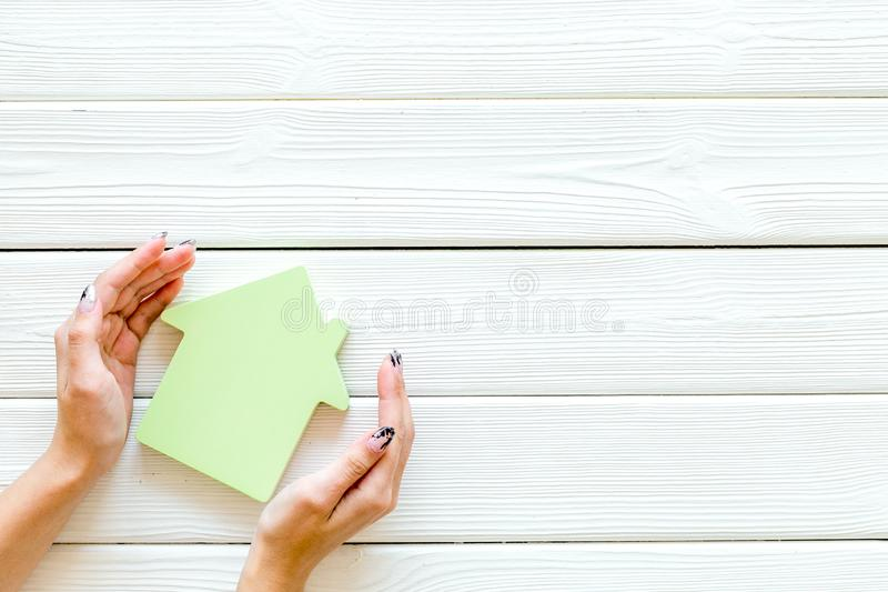 Search for a new house concept with house figure in hands on white wooden office desk background top view space for text.  royalty free stock photography