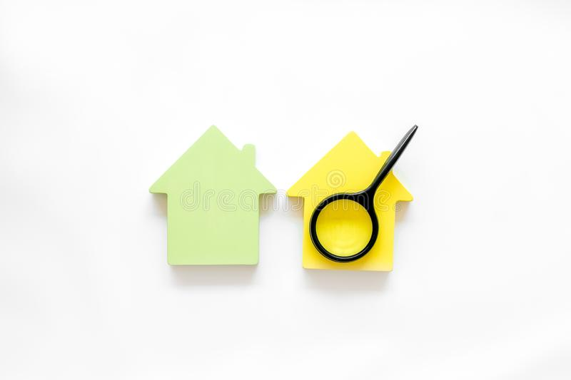 Search for a new house concept with house figure and magnifier on white office desk background top view.  royalty free stock photography