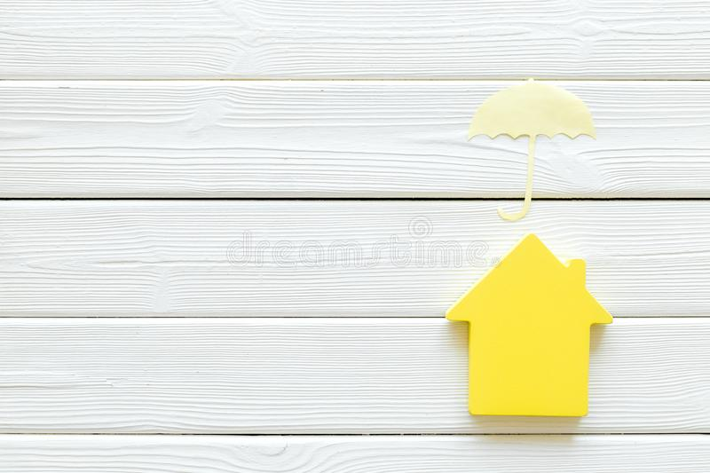 Search for a new house concept with house and umbrella figure on white wooden office desk background top view.  stock photo