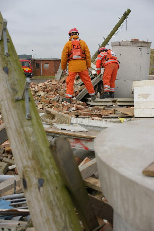 Search & rescue disaster zone. Search & rescue fire-fighters at building collapse royalty free stock photo