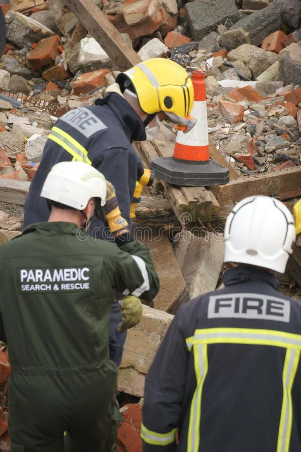 Search & rescue disaster zone. Search & rescue fire-fighters at building collapse stock photography