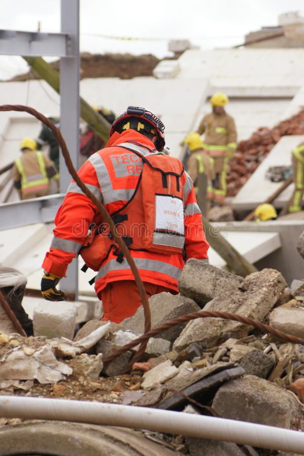 Search & rescue disaster zone. Search & rescue fire-fighters at building collapse stock photo