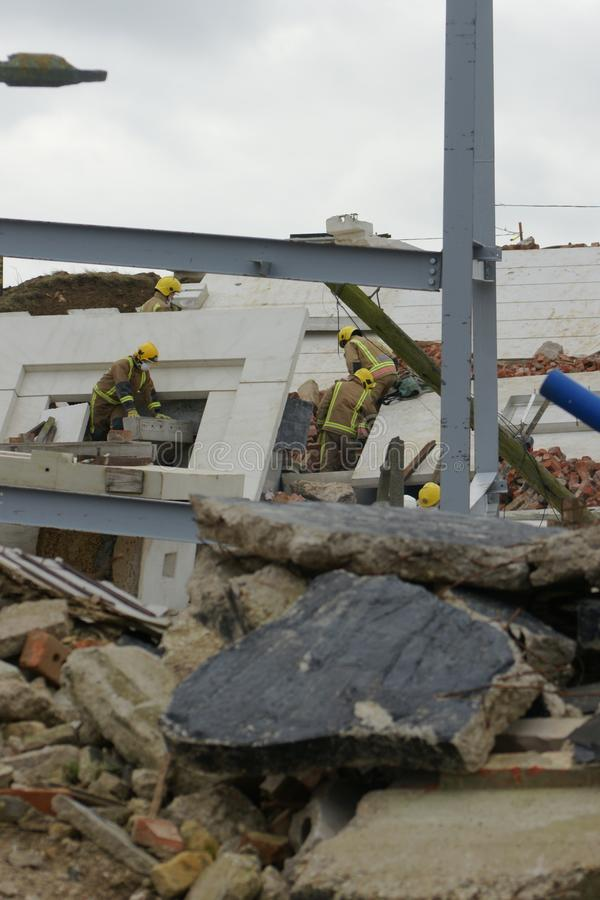 Search & rescue disaster zone. Search & rescue fire-fighters at building collapse stock photos