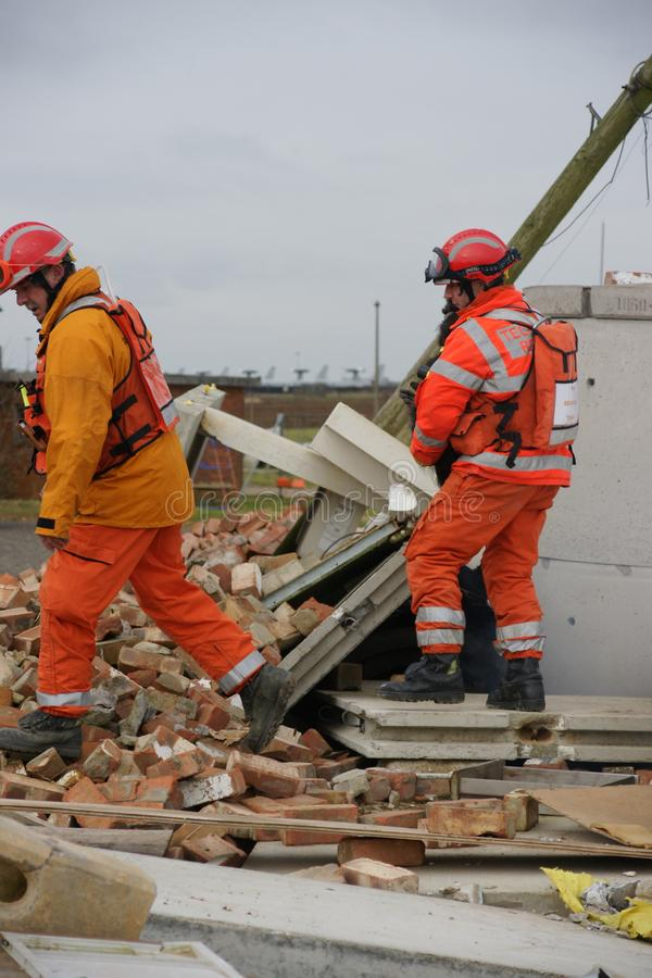 Search & rescue disaster zone. Search & rescue fire-fighters at building collapse stock image