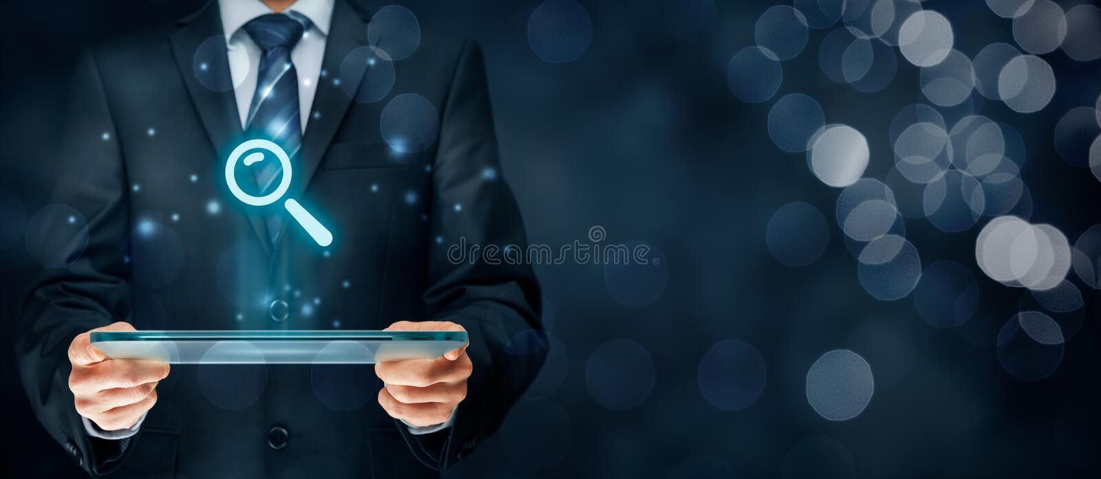 Search and SEO. Search, find and SEO internet concepts. Businessman hold futuristic tablet with head-up display and symbol of loupe stock image