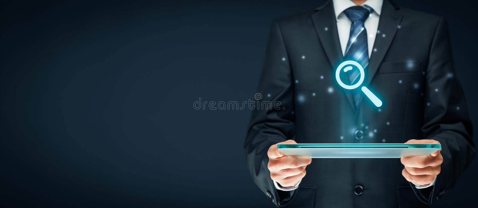 Search and SEO. Search, find and SEO internet concepts. Businessman hold futuristic tablet with head-up display and symbol of loupe stock photos