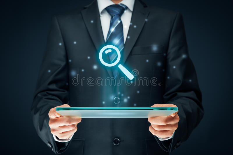 Search and SEO. Search, find and SEO internet concepts. Businessman hold futuristic tablet with head-up display and symbol of loupe stock photography