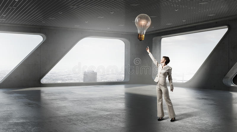 She is in search of solution. Businesswoman on top floor of modern building against office window royalty free stock photo