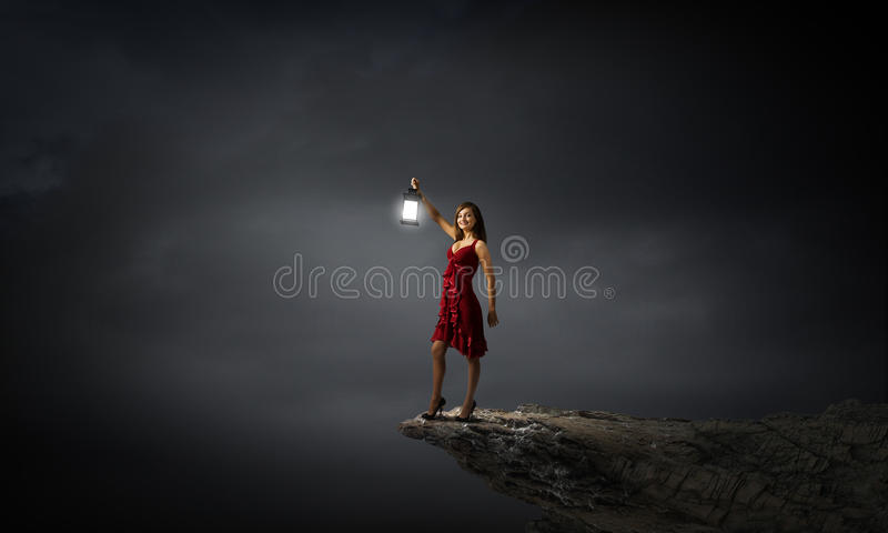 In search of something. Young attractive woman in red dress with lantern walking in darkness stock photography