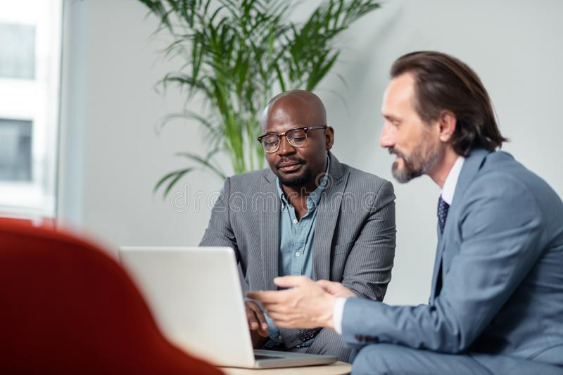 Business partners using laptop while searching information for project royalty free stock photos