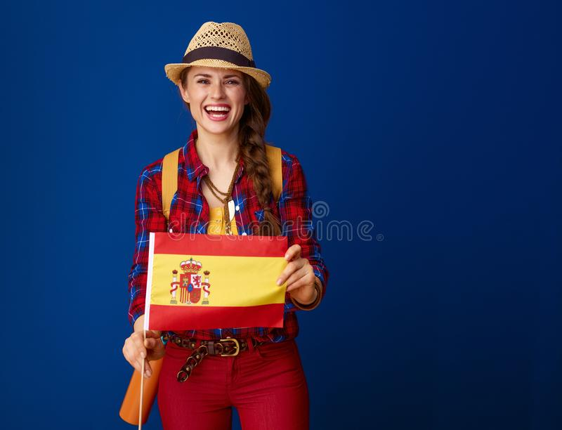 Tourist woman against blue background showing flag of Spain stock image